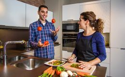 Woman cutting vegetables while husband juggles tomatoes. Woman cutting vegetables to prepare food while her husband juggles tomatoes Royalty Free Stock Images