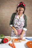 Woman cutting vegetables on wooden board stock image