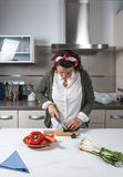 Woman cutting vegetables on wooden board royalty free stock image