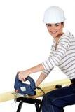 Woman cutting wood Royalty Free Stock Image
