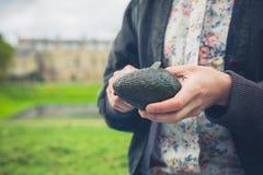Woman cuttting avocado outdoors Royalty Free Stock Image