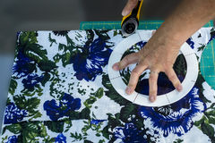 Woman cuttting fabric. With a rotary knife on a cuutting board Royalty Free Stock Image