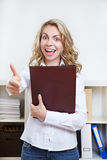 Woman with CV holding thumbs up. Cheering happy woman with her CV holding her thumbs up Royalty Free Stock Images
