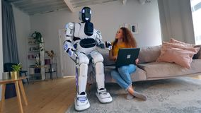 Woman and cyborg work with a laptop, sitting on a couch. Robot and human cooperation. stock video footage