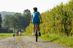 A woman on a cycle catching up with her friends in front. Royalty Free Stock Photos