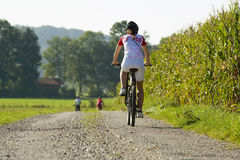 A woman on a cycle catching up with her friends in front. Stock Image
