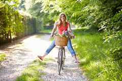 Woman On Cycle Ride In Countryside. With Flowers In Basket Having Fun Royalty Free Stock Image