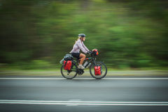 A woman cycles along a road in New South Wales, Au Stock Image