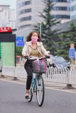 Woman cycles with mouth cloth as protection, Kunming, China Stock Image