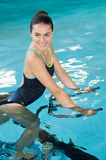 Woman cycling aqua bike. Fit smiling woman cycling on aqua bike in swimming pool. Smiling young woman using under water exercise bike in the swimming pool. Happy Royalty Free Stock Photos