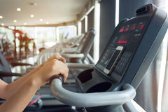 Woman cycling burn fat on bicycle cardio machine in fitness gym. Close-up hand woman cycling burn fat on bicycle cardio machine in fitness gym exercise sport Stock Photography