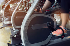 Woman cycling burn fat on bicycle cardio machine in fitness gym Stock Photo