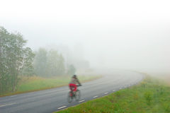 Woman cycling on foggy morning Stock Photos