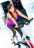 Woman cycling at the gym Stock Photography