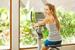 Woman cycling in gym Stock Photography