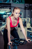 Woman cycling in a gym, wearing in sportswear. Stock Photography