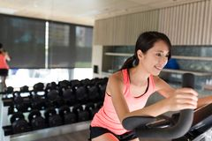 Woman cycling on machine in gym Stock Photos