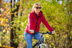 Woman cycling. Mature woman cycling in park Royalty Free Stock Images