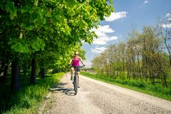 Woman cycling a mountain bike in city park, summer day. Woman cycling a mountain bike in a city park, summer day. Inspire and motivate concept for outdoors stock images