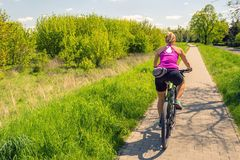 Woman cycling a mountain bike in city park, summer day. Woman cycling a mountain bike in a city park, summer day. Inspire and motivate concept for outdoors stock photo