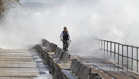 Woman cycling next to sea during strong coastal waves Stock Photography