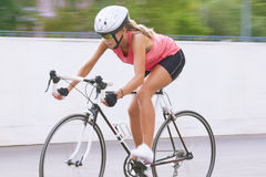 Woman cycling outdoors Stock Photo
