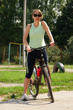 Woman cycling in a park. Sunny day Stock Photos