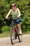 Woman cycling in a park Stock Image