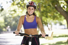 Woman Cycling Through Park Stock Images