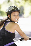 Woman Cycling Through Park Stock Image