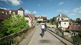 Woman cycling on road through village in France stock video