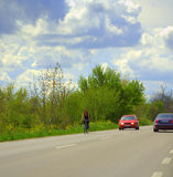 Woman cycling  spring road scenery Royalty Free Stock Photography