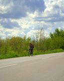 Woman cycling spring road Stock Photography
