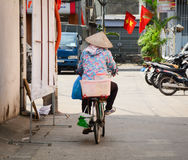 A woman cycling on the street Stock Photography