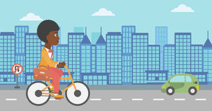 Woman cycling to work. An african-american woman with a briefcase cycling to work on city background vector flat design illustration. Horizontal layout Royalty Free Stock Photos