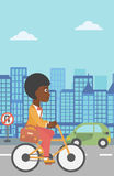 Woman cycling to work. An african-american woman with a briefcase cycling to work on city background vector flat design illustration. Vertical layout Royalty Free Stock Photography