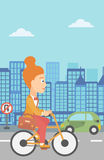 Woman cycling to work. A woman with a briefcase cycling to work on city background vector flat design illustration. Vertical layout Royalty Free Stock Photo