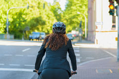 Woman cycling to work in a city Stock Images