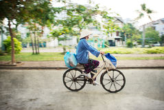 Woman cycling with traditional Vietnamese hat Royalty Free Stock Images
