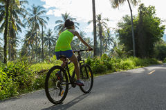 Woman cycling on tropical forest trail Royalty Free Stock Photography