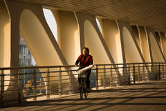 Woman cycling under a bridge with French taste Stock Photography