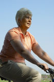 Woman cyclist. Retired woman enjoys cycling in the countryside stock photo