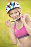 Woman cyclist against the background of green grass. Beautiful woman cyclist against the background of green grass Royalty Free Stock Photo