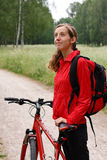Woman cyclist on a bicycle walk on the park. Woman cyclist with bike and backpack in a red tracksuit on a bicycle walk on the park Royalty Free Stock Photography