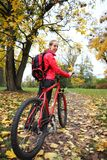 Woman cyclist with bike and backpack bicycle walk in park Stock Photography