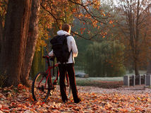 Woman cyclist with bike and backpack in park. Woman cyclist with bike and backpack in autumn park, lit morning sun Stock Photography