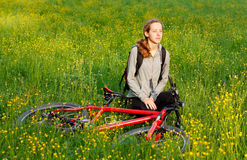 Woman cyclist with bike among the blooming meadow Stock Photo