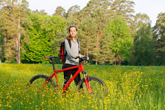 Woman cyclist with bike among the blooming nature Stock Photo