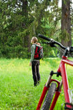 Woman cyclist with bike among the green nature Stock Photo