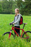 Woman cyclist with bike among the green nature Royalty Free Stock Photos